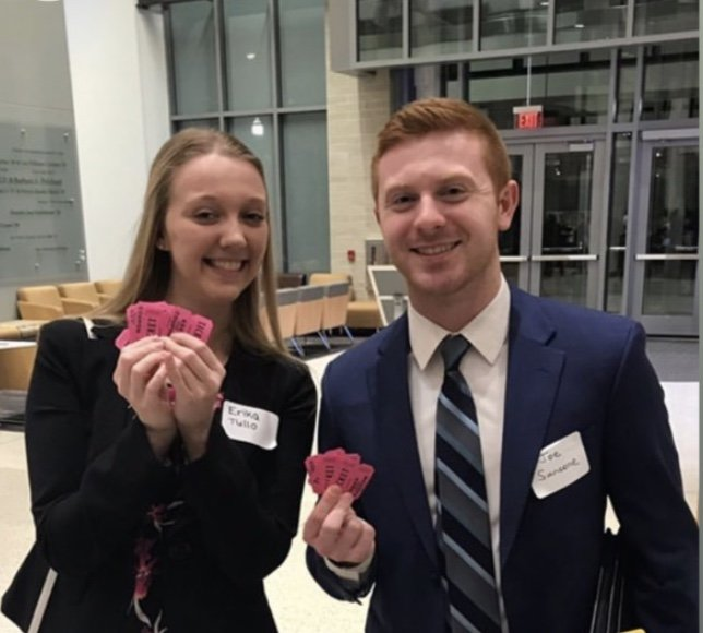 Joe Sansone standing next to a woman holding pink raffle tickets.