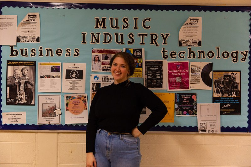 Bianca stands in front of a Music Industry bulletin board.