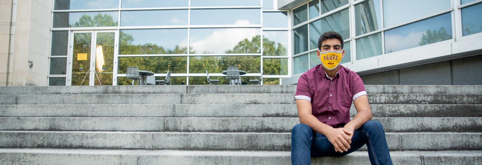 Bhavik sits on the steps of Engineering Hall wearing a mask.