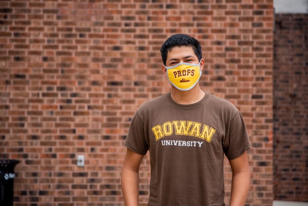 """Erwin stands in front of a brick wall with his """"Profs"""" mask on."""