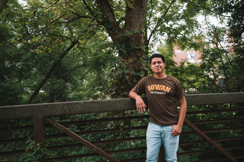 Erwin stands on a footbridge wearing a Rowan t-shirt.