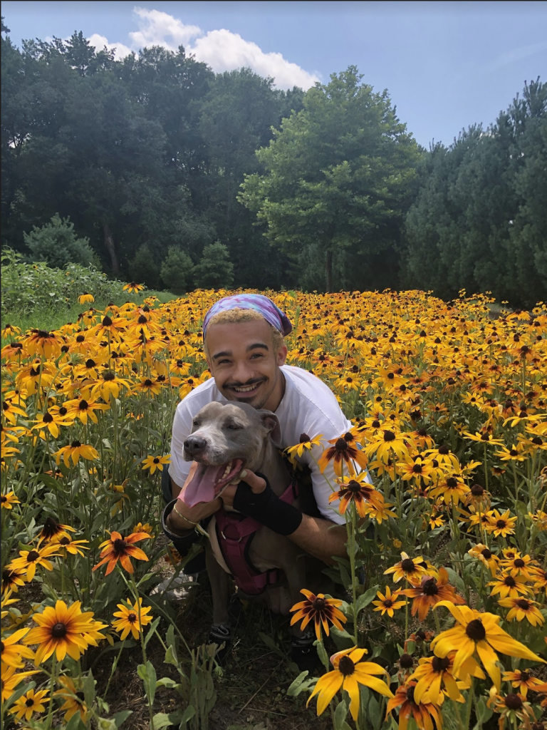 Isaiah holding a dog in the middle of a flower field.