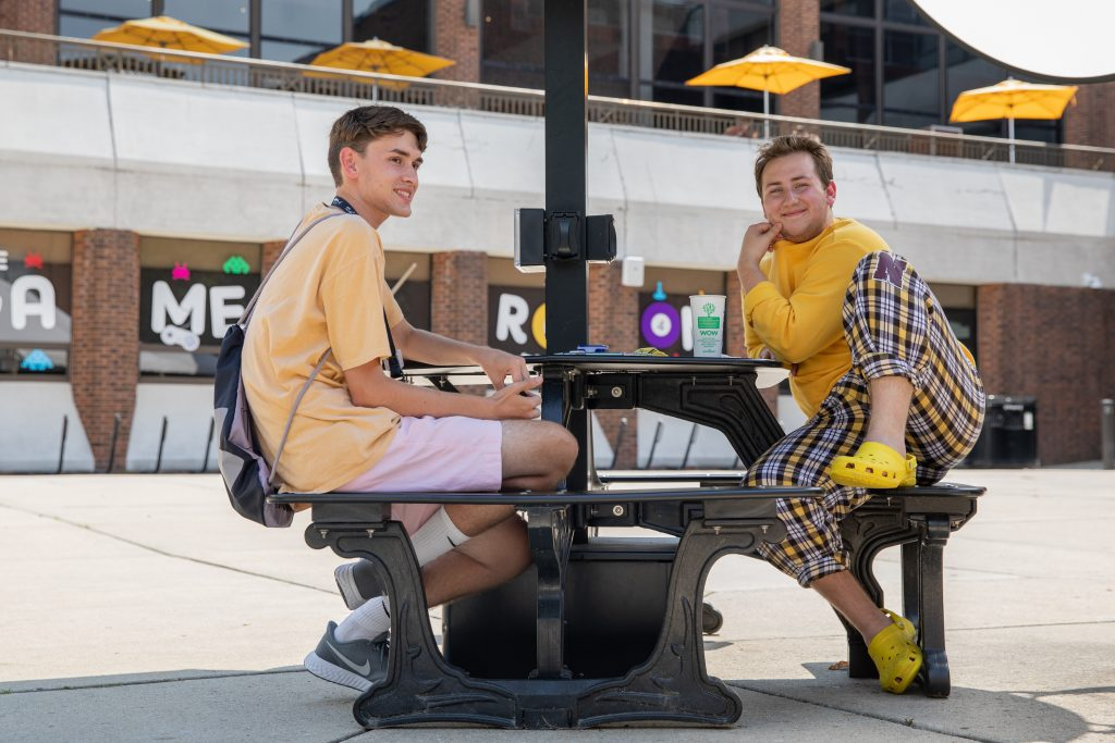 Connor and Ben sitting with each other outside the student center.
