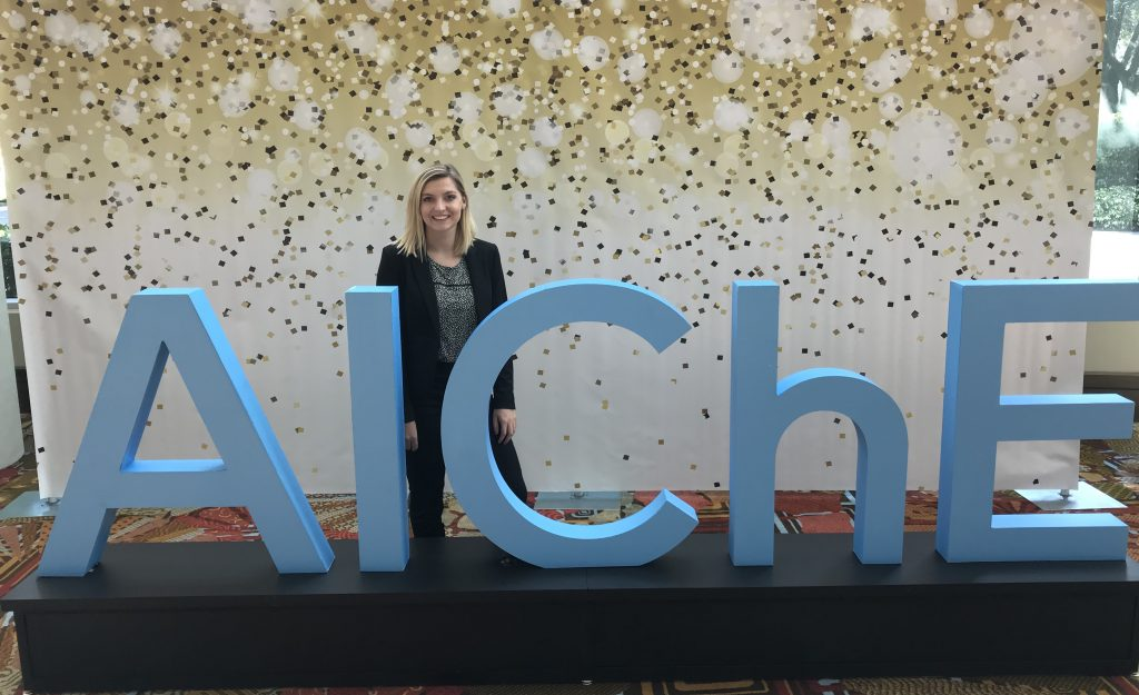 "Tori posing with a sign that says ""AlChe""."