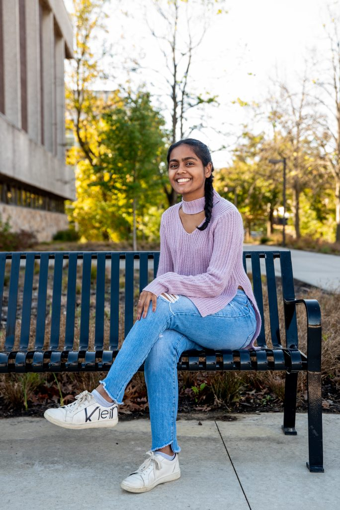 Alisa siting on a bench near Robinson Hall, trees in the background.