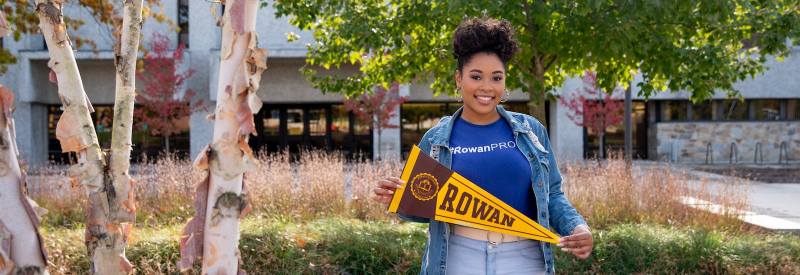 College of Education student Cheyenne holds a pennant on campus.