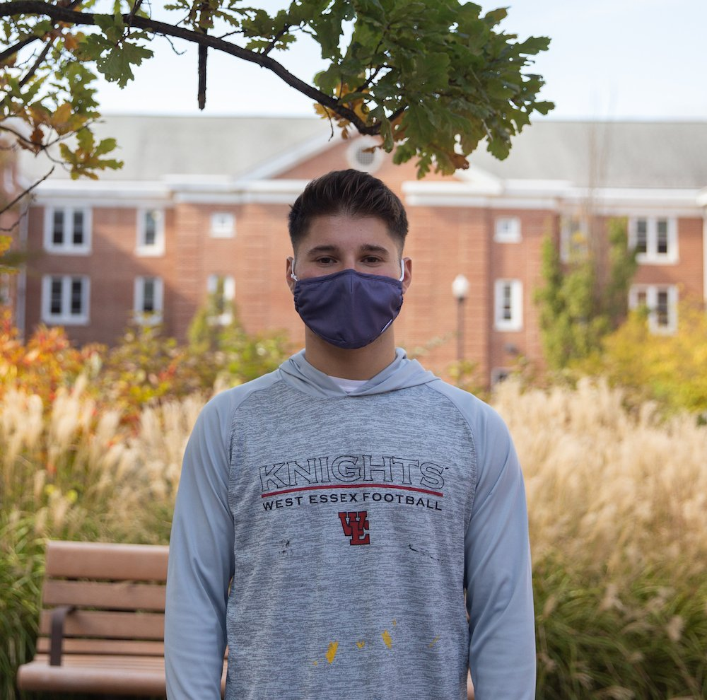 Chris poses in front of Chestnut Hall wearing a blue mask. Green and white shrubbery around him. Tree branch above him.