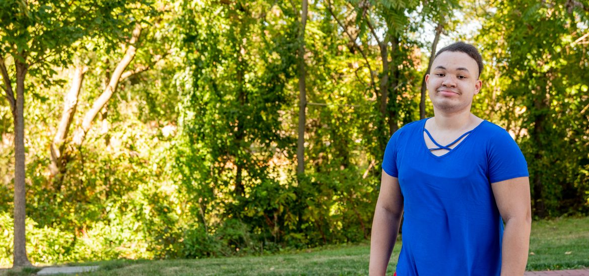 Christine standing outside in front of trees in a blue shirt.