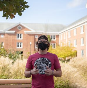 Griffin gives a double thumbs up wearing a black mask and a black backwards hat. Chestnut hall is in the background.
