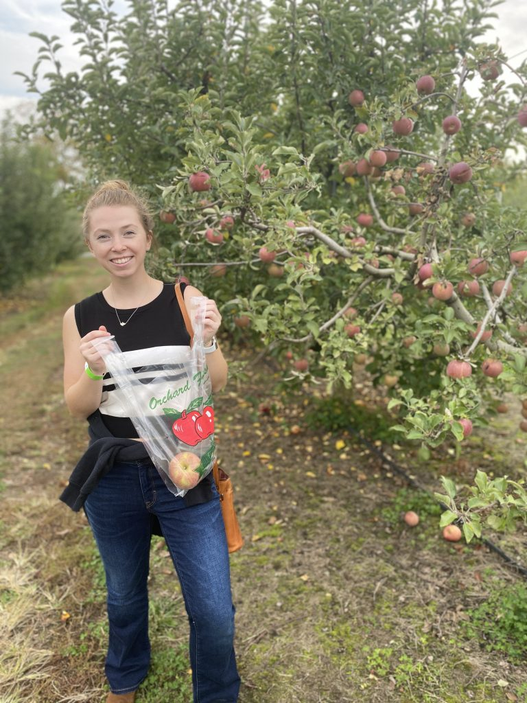 Olivia smiling and picking apples.