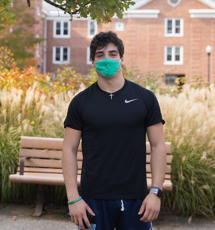 Noah poses in front of Chestnut hall wearing a green mask. There is green and white shrubbery around him. There are benches behind him.