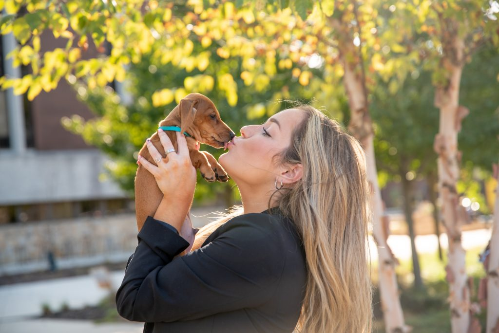 Slinky the dachshund giving his owner Sarah a kiss outside.