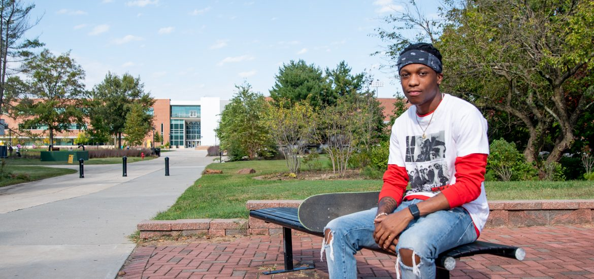 McCarly sits on a bench on campus outside.