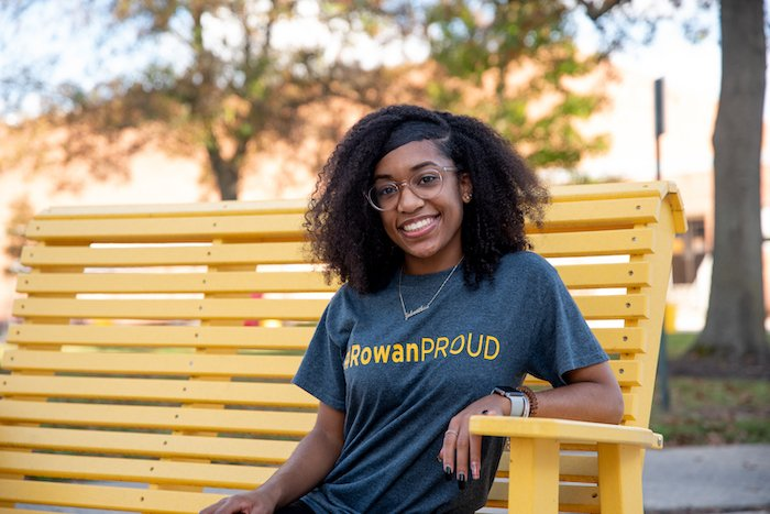 Tyra sitting on a yellow bench on Rowans campus.