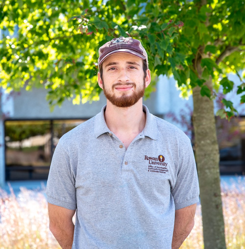 Will stands in front of tree and ornamental grass on campus.
