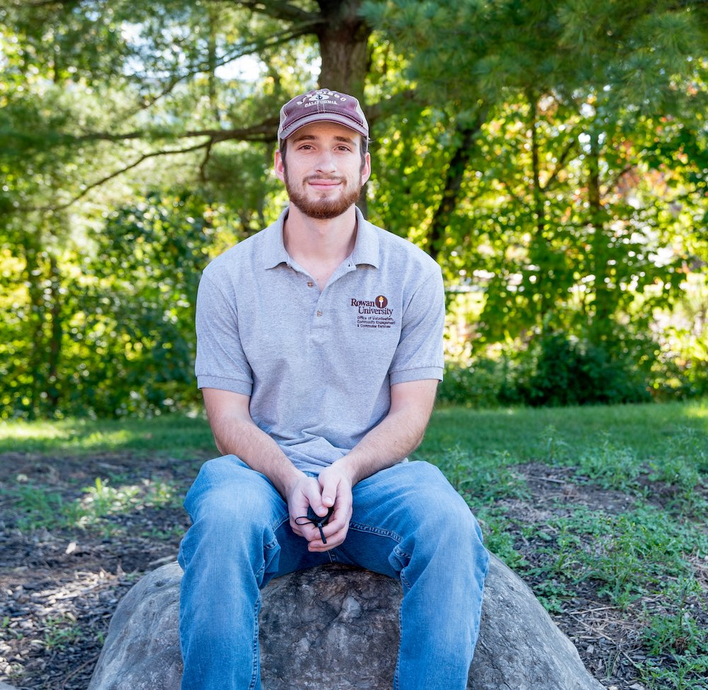 Will sits on a stone in front of trees on campus.