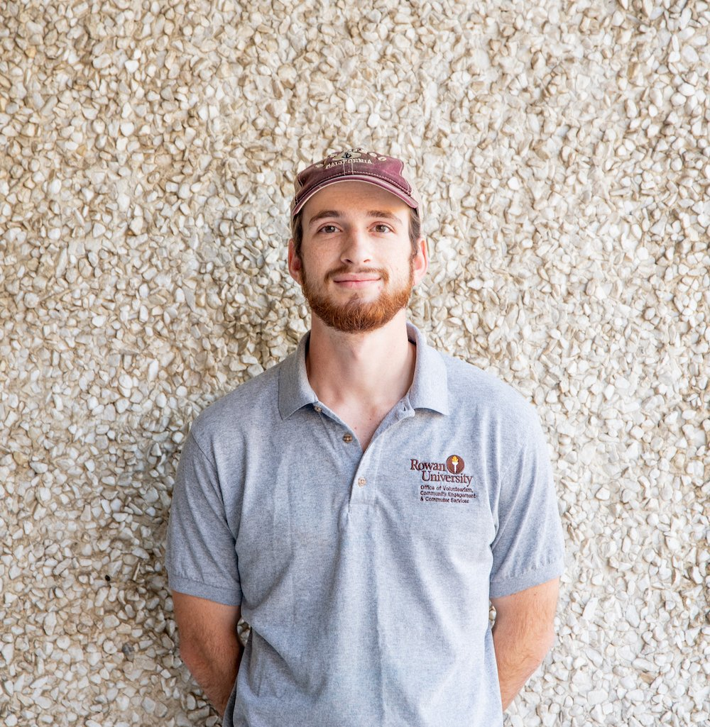 Will stands in front of textured wall on campus.