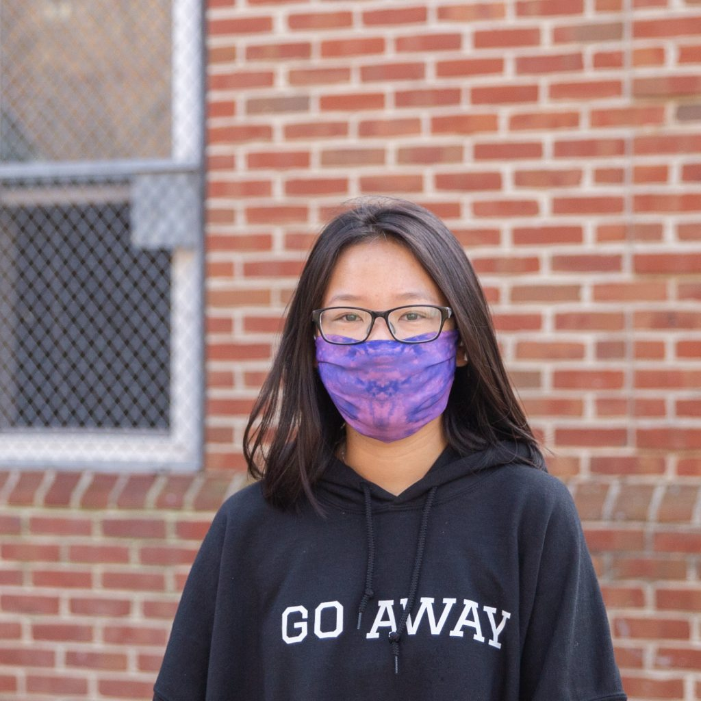 Lili poses in a purple mask in front of a brick building.
