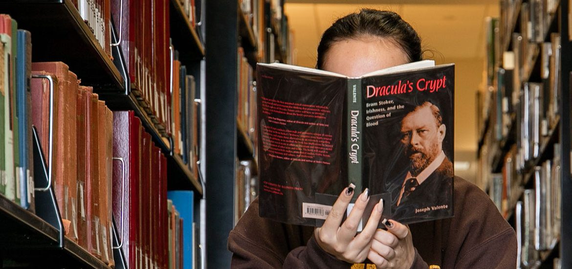 Student reads a book in the stacks of Campbell Library.