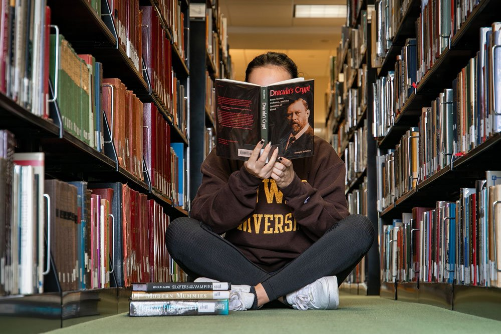 Student reads inside Campbell Library.
