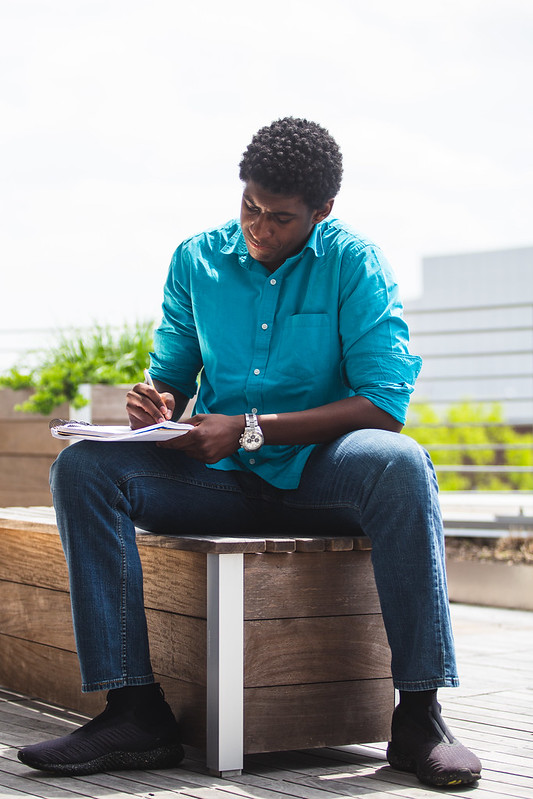 Student studies outside on campus.