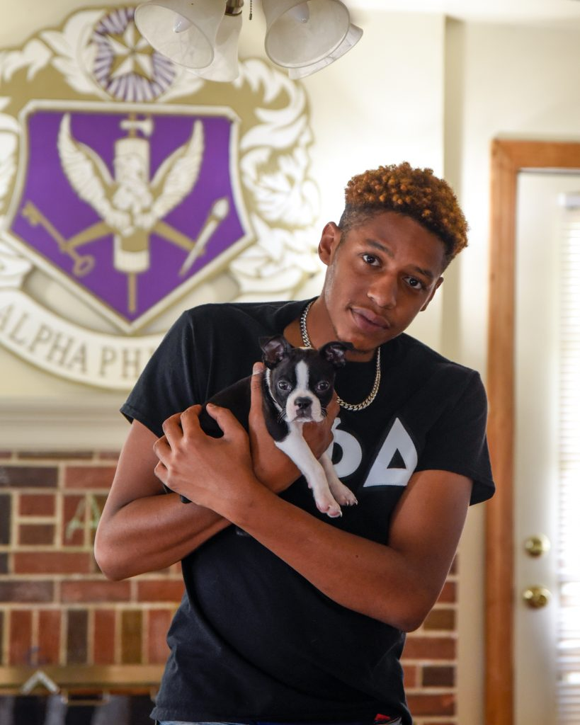 Justice holding a small black and white puppy in front of a Fraternity insignia.