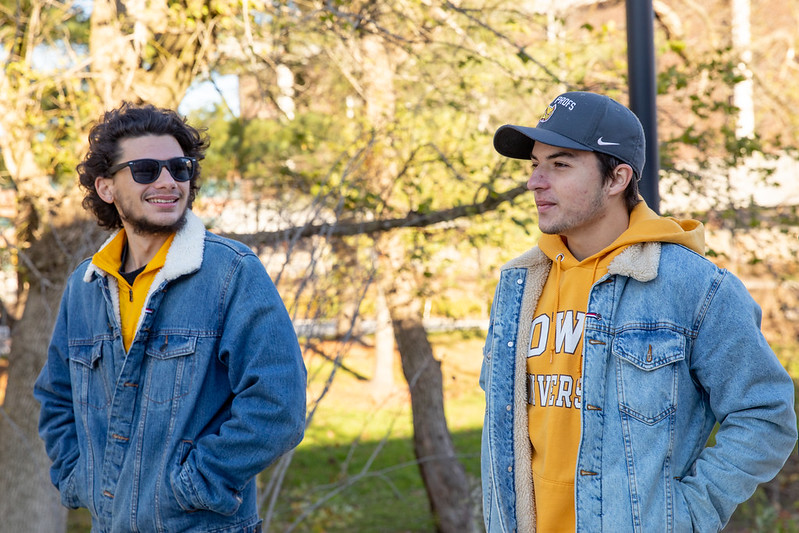 Two students in denim jackets talk and walk on campus.