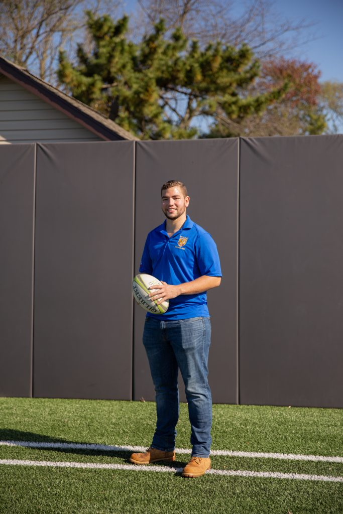 Chase poses on the intramural field with a rugby ball.