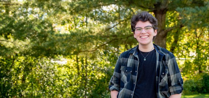 Elliot stands in a wooded area on campus.