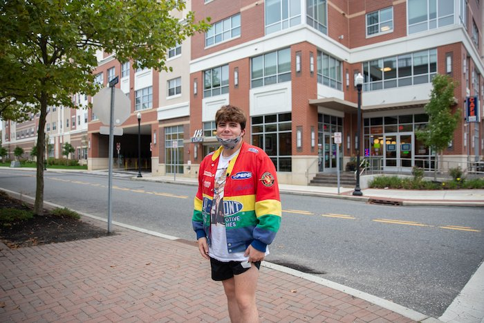 Nick posing by 114 Victoria wearing a rainbow jacket.