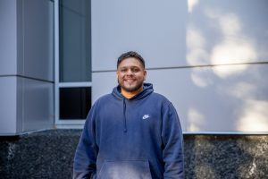 Martin smiles standing in front of Wilson Hall while wearing a navy blue sweatshirt.