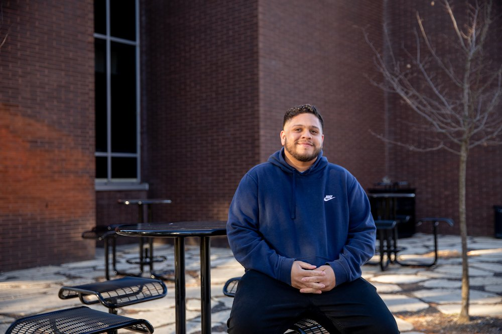 Martin Gonzalez sits at a table in front of Wilson Hall wearing a navy blue sweatshirt.