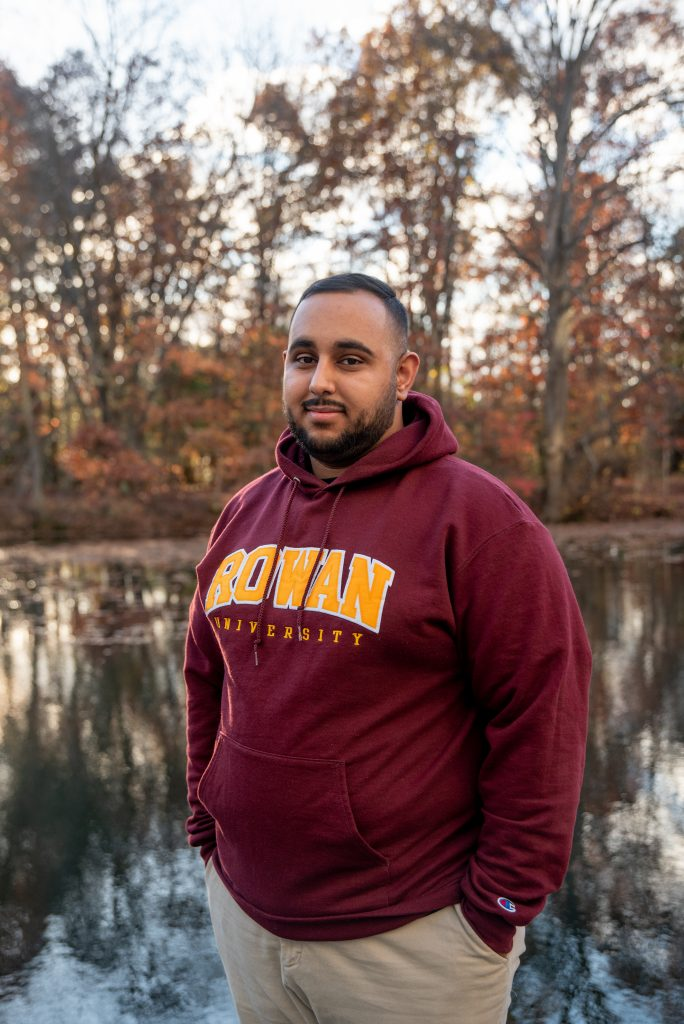 Muhammad standing in front of a pond in a Rowan sweatshirt.