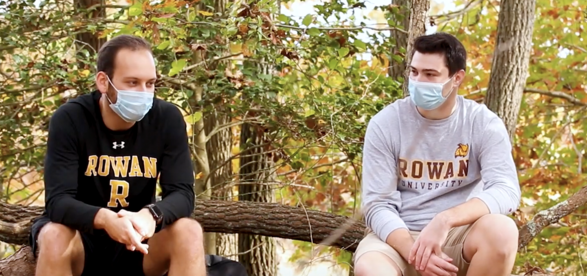 Two students in Rowan gear sit at the nature preserve.