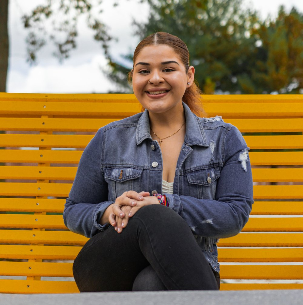 Shirley Celi-Landeo poses wearing a denim jacket while smiling on a yellow bench.