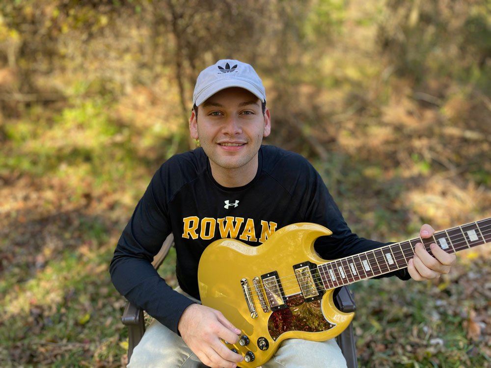 Author Max wears a Rowan shirt and holds a yellow guitar.