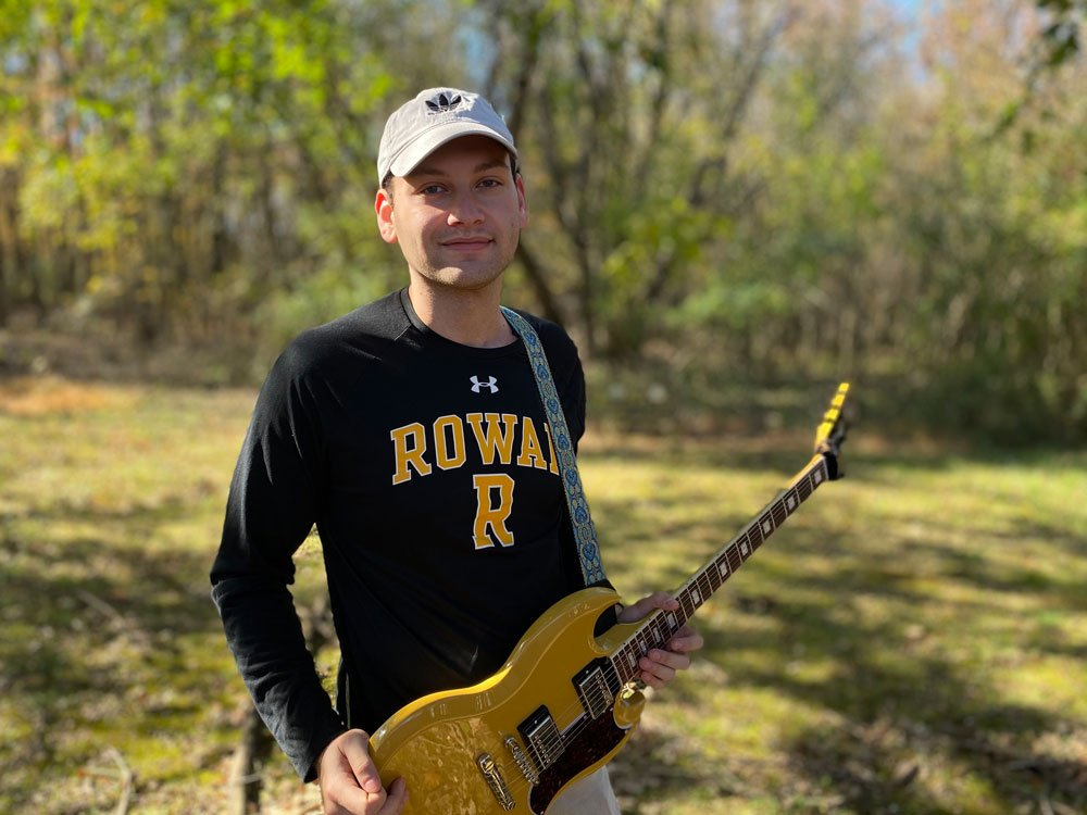 Max wears a Rowan t-shirt and holds a yellow guitar.
