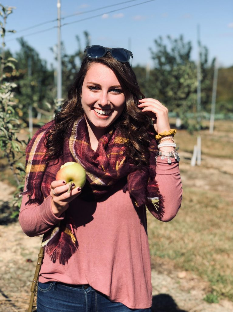 Alexa smiling and holding an apple in an apple orchard.
