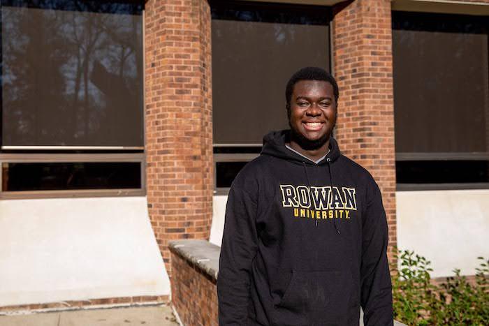 Gregory outside the student center wearing a Rowan sweatshirt.