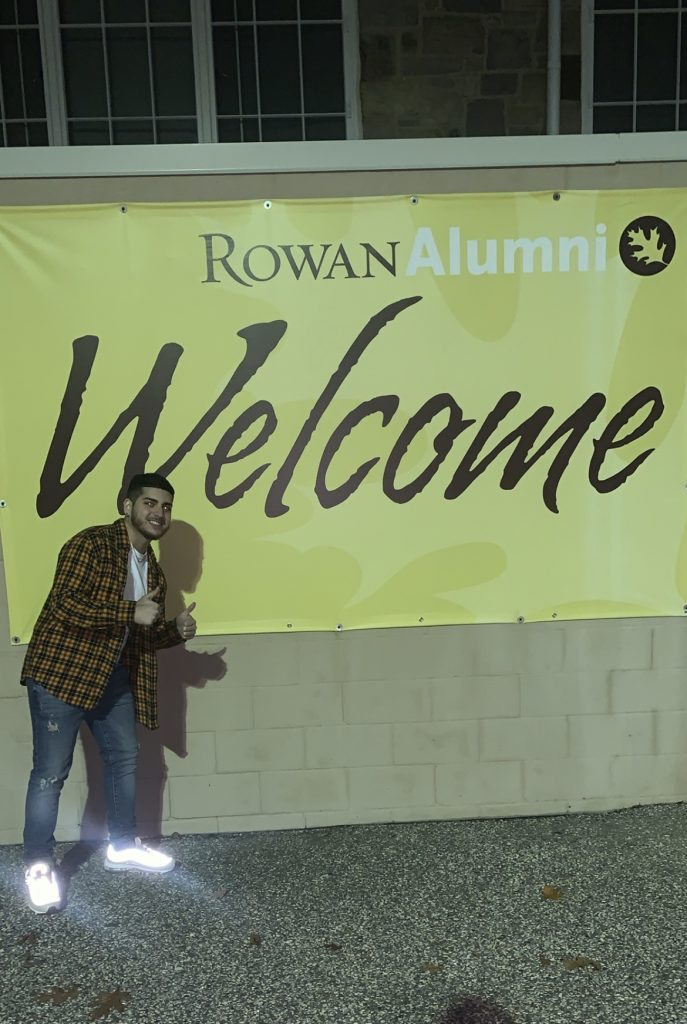 "Matthew poses with a ""Rowan Alumni Welcome"" sign."