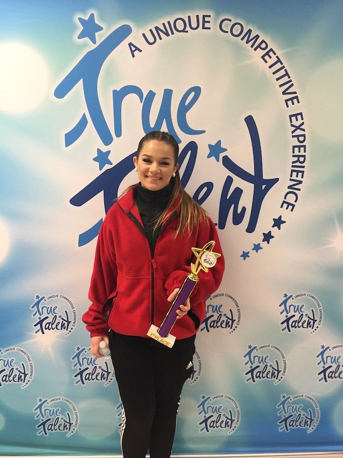 Abby holding a trophy from a dance competition.