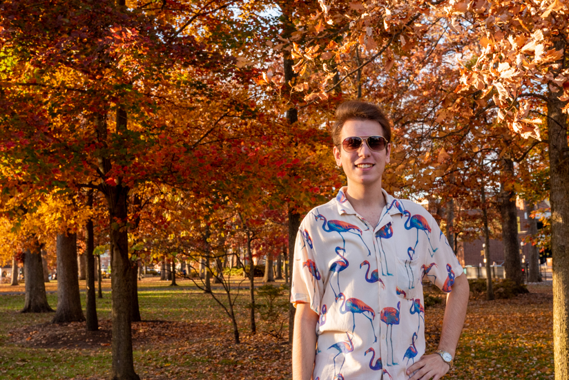 Brett standing outside with fall foliage in the background.