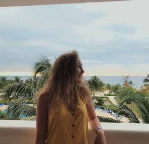 Emily looks over her shoulder, with a view of sand, beach and palm trees in the background.