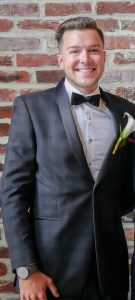 Sal poses in a tuxedo with brick behind him.