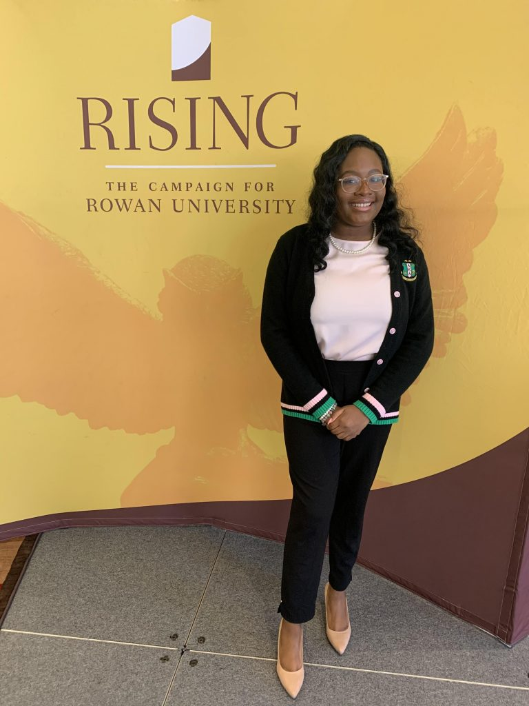 Arielle poses next to a Rowan campaign backdrop in her Alpha Kappa Alpha attire.