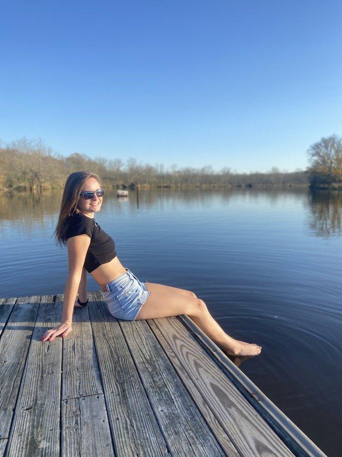Haley sitting on a doc on a lake.