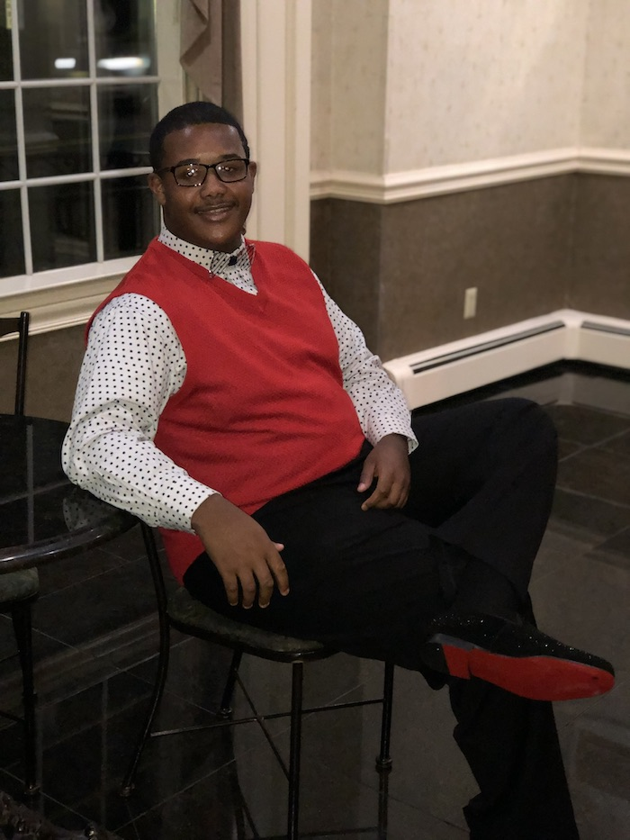 Jamar sitting on a chair while wearing a red sweater and red bottomed shoes.