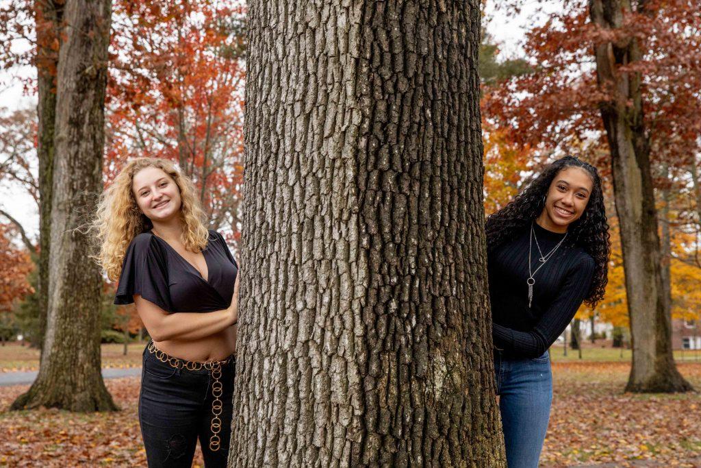 Jayshalie and her friend standing around a tree.