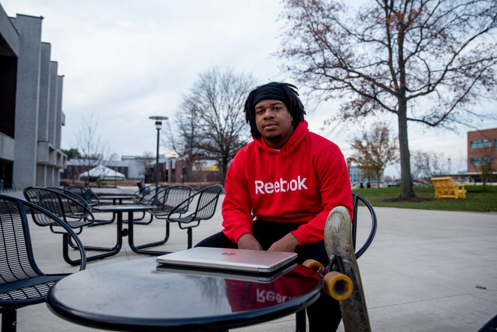 Jaylen poses with his laptop and skateboard, sitting at a table outside.