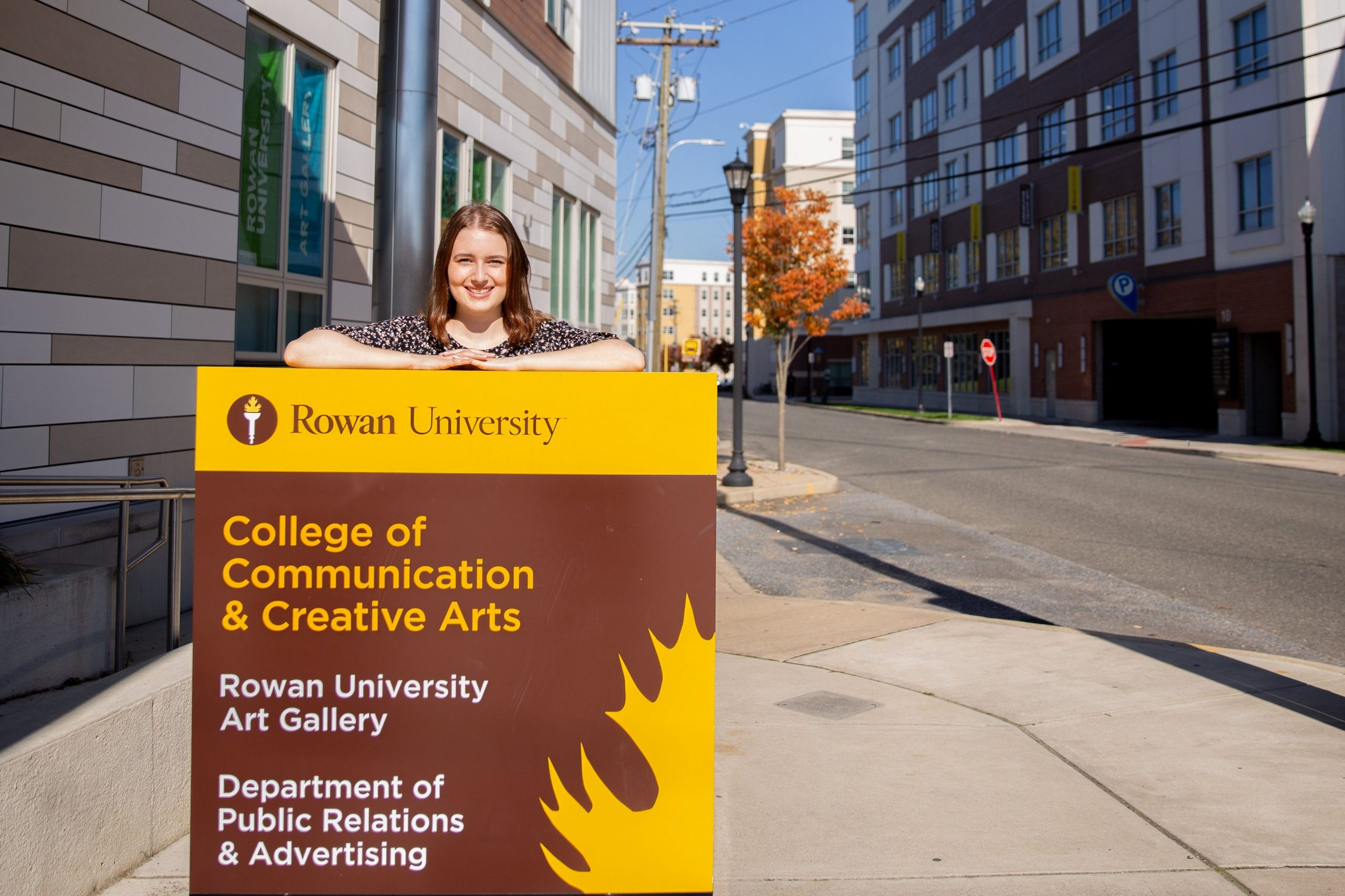 Jessica poses with a sign in front of 301 high street.